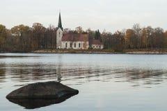 Paisaje del otoño con la iglesia a través del río en puesta del sol Imagen de archivo libre de regalías