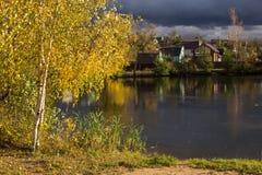 Paisaje del otoño de las casas del pueblo en la orilla del lago Campo en el tiempo de caída Árbol de abedul con las hojas amarill Imagen de archivo