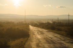 Paisaje del otoño o del invierno con el camino y los árboles La puesta del sol de los haces luminosos del oro En un fondo de las  Foto de archivo libre de regalías