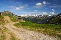 Paisaje del paisaje en las montañas con un camino hermoso y una choza de la montaña Imagen de archivo libre de regalías