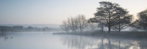 Paisaje del panorama del lago en niebla con resplandor del sol en la salida del sol foto de archivo