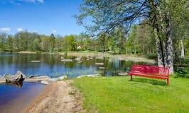 Paisaje del panorama del lago spring con el banco rojo simbólico Foto de archivo libre de regalías