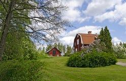 Paisaje del parque con las casas de madera rojas Imagen de archivo