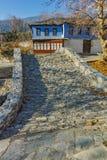 Paisaje del pueblo con la casa y el puente viejos de la piedra en Moushteni cerca de Kavala, Grecia Foto de archivo