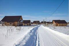 Paisaje del pueblo con las cabañas de madera en día de invierno soleado foto de archivo