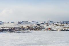 Paisaje del pueblo con las casas en invierno en la orilla del lago Baikal y las naves en el hielo en un fondo montañoso nevoso Fotografía de archivo libre de regalías