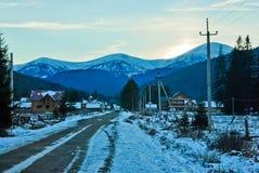 Paisaje del pueblo de montaña con las casas de madera en la puesta del sol Imagen de archivo libre de regalías