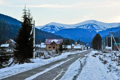 Paisaje del pueblo de montaña con las casas de madera en la puesta del sol Imágenes de archivo libres de regalías