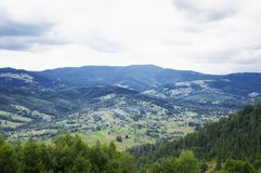 Paisaje del pueblo del valle verde de la monta?a nublado fotografía de archivo libre de regalías