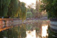 Paisaje del río en el parque de la ciudad en la puesta del sol imagenes de archivo