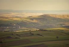 Paisaje del verano con el árbol y la aldea de las colinas en el ev Foto de archivo