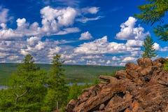 Paisaje del verano con el río, el bosque, los acantilados y las nubes en el cielo azul Foto de archivo libre de regalías