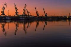 Paisaje del verano con el río, los barcos de motor y las siluetas de grúas en el puerto Foto de archivo libre de regalías