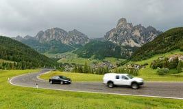 Paisaje del verano de Dolomiti con los pueblos en la ladera herbosa de las montañas y de los coches rugosos que viajan en una ca imagenes de archivo