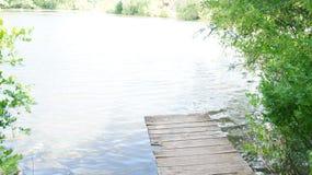 Paisaje del verano, puente en la orilla de la charca Foto de archivo libre de regalías