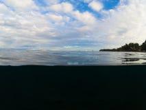 Paisaje doble con el mar y el cielo Por encima y por debajo de la línea de flotación en costa tropical Fotos de archivo
