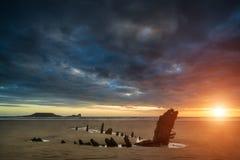 Paisaje dramático hermoso de la puesta del sol sobre naufragio en Rhosilli Imagen de archivo libre de regalías