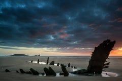 Paisaje dramático hermoso de la puesta del sol sobre naufragio en Rhosilli B Imagen de archivo