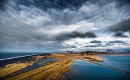 Paisaje en Islandia con agua del océano, las rocas y la playa negra de la arena Cielo nublado y camino Fotografía de archivo