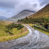 Paisaje escocés típico con las nubes y el arco iris pesados Imágenes de archivo libres de regalías