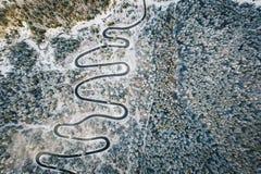 Paisaje estacional de una carretera con curvas rodeada por la nieve en el bosque fotos de archivo libres de regalías