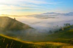 Paisaje fantástico en las montañas en la salida del sol con niebla Backg Foto de archivo
