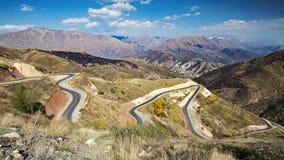Paisaje hermoso con el camino rural largo que lleva a través de las colinas fotos de archivo