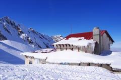 Paisaje hermoso con la cabina alpina, el cielo azul y la sol en invierno Montañas de Fagaras imágenes de archivo libres de regalías