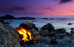 Paisaje hermoso con la hoguera en la playa en la puesta del sol Imagenes de archivo
