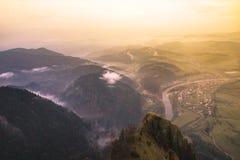 Paisaje hermoso con las montañas en la niebla en la puesta del sol, debajo de t foto de archivo