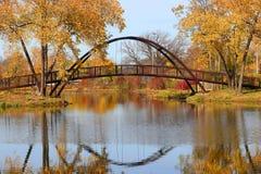Paisaje hermoso de la caída con un puente en el parque de la ciudad foto de archivo