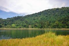 Paisaje hermoso de la Laguna Verde con un barco, en Apaneca, itinerario de Ruta de Las Flores, El Salvador Fotos de archivo