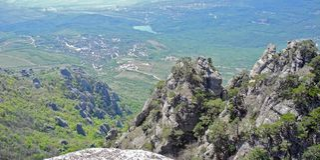 Paisaje hermoso de la montaña con vista superior de un valle distante con el lago Distante en una neblina azul Montañas crimeas imágenes de archivo libres de regalías