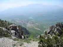 Paisaje hermoso de la montaña con vista superior de un valle distante con el lago Mesetas distantes de la montaña en una neblina  foto de archivo libre de regalías