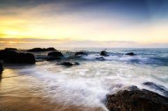 Paisaje hermoso de la opinión del mar sobre fondo imponente de la salida del sol el haz de la luz del sol y la onda suave que gol Imagen de archivo libre de regalías