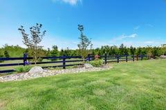 Paisaje hermoso de la primavera del patio trasero con la cerca y el bosque. Fotos de archivo libres de regalías