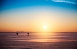 Paisaje hermoso de la puesta del sol del invierno con los esquiadores a campo través Foto de archivo libre de regalías