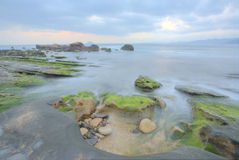 Paisaje hermoso de la salida del sol por la costa rocosa Fotos de archivo