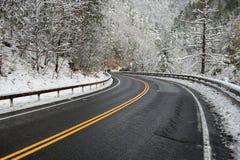 Paisaje hermoso del invierno con el camino de la carretera con vuelta y los árboles nevados Fotos de archivo