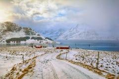Paisaje hermoso del invierno con las chozas noruegas tradicionales de la pesca en las islas de Lofoten, Noruega Imagen de archivo