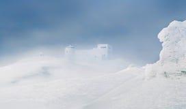 Paisaje hermoso del invierno con las colinas nevosas y el observ abandonado Fotos de archivo libres de regalías