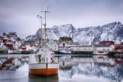 Paisaje hermoso del invierno del puerto con el barco de pesca y el rorbus noruego tradicional Imagenes de archivo