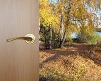 Paisaje hermoso del otoño después de la puerta de madera con la manija del metal amarillo Fotografía de archivo libre de regalías