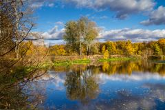 Paisaje hermoso del otoño - visión desde la orilla del río con la reflexión en agua Imagen de archivo libre de regalías
