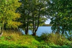 Paisaje hermoso del otoño Vista del lago glacial antiguo rodeado por los árboles foto de archivo