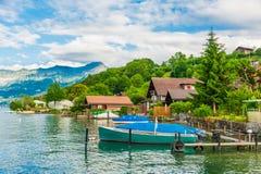 Paisaje hermoso del verano con el lago, las montañas, las casas y un barco Imagen de archivo