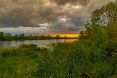 Paisaje hermoso del verano Nubes púrpuras brillantes sobre la superficie del río Imagenes de archivo