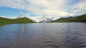 paisaje hermoso fabuloso con las ondas en el lago en las montañas suizas, Europa Wetterhorn, Schreckhorn, Finsteraarhorn y Bachse almacen de metraje de vídeo