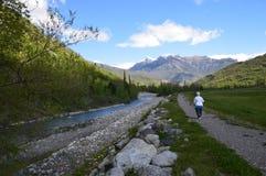 Paisaje hermoso, mujer que camina además de un río Foto de archivo