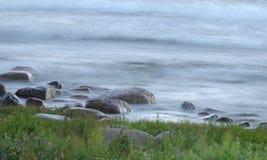 Paisaje hermoso - piedras, hierba y ondas del mar Foto de archivo libre de regalías